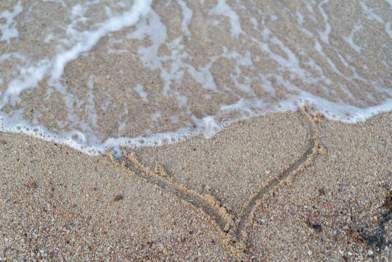 无情的爱和伤心的概念 波浪洗涤被绘的心脏 库存图片