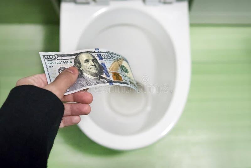 无意义的浪费金钱,损失,无用的废物的概念,大水花费, 100美金被冲洗入马桶 库存照片