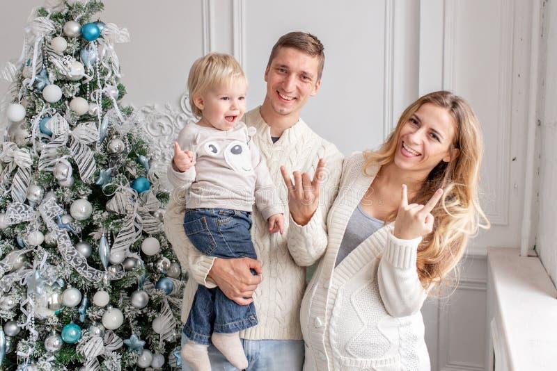 无所事事在照相机 在家庭的父亲、怀孕的母亲和他们的小儿子的愉快的家庭画象 新年好 库存照片