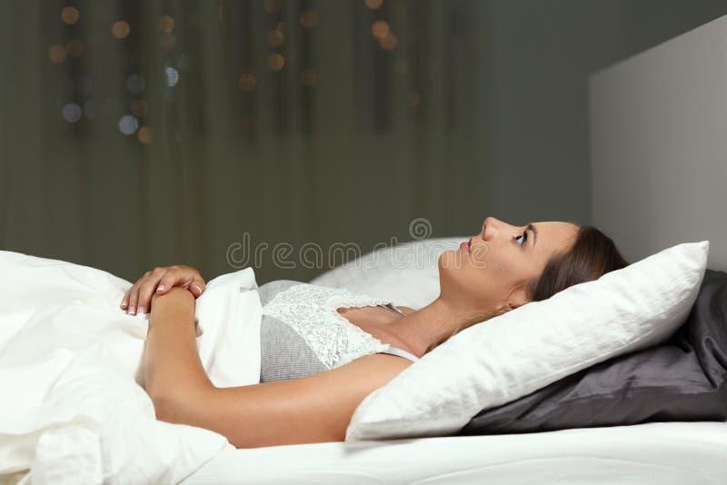 无法失眠的女孩在床上的夜睡觉 免版税库存照片