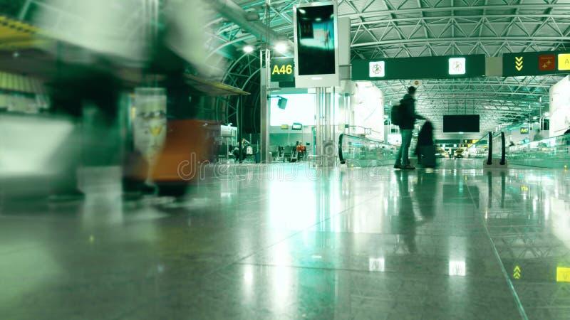 无法认出的乘客在普通机场终端走 长的风险射击 库存图片