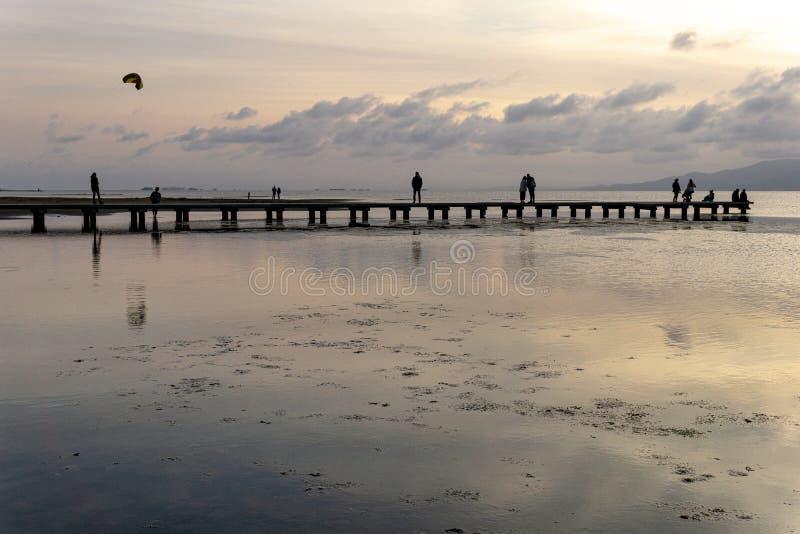 无法认出的人剪影一个码头的在日落 免版税库存照片