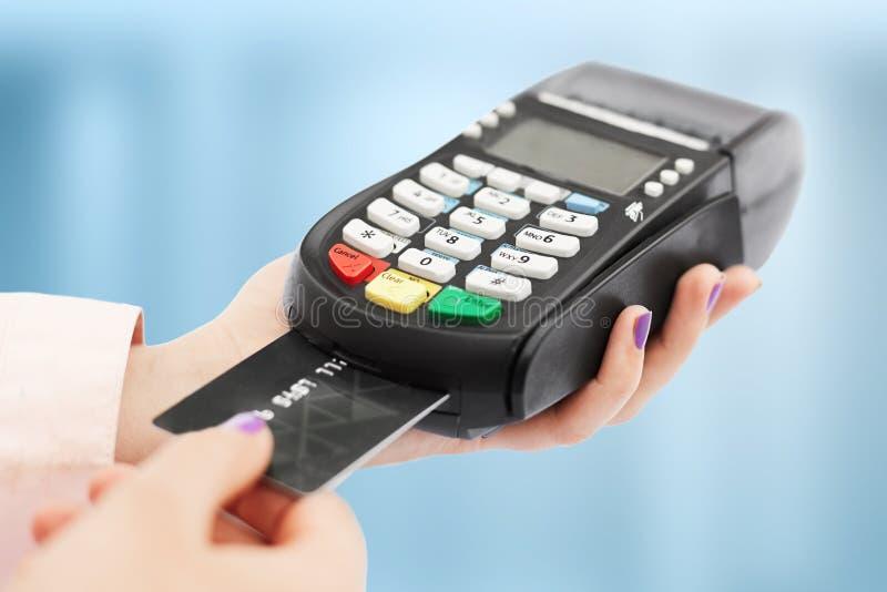 无法认出的妇女举行猛击机器,并且信用卡,支付购买,在商店使用银行终端,被隔绝在蓝色后面 库存照片