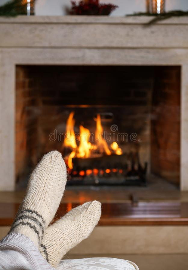 无法认出的妇女的脚或人温暖的白色被编织的袜子的和格子花呢披肩在壁炉前面 舒适轻松不可思议 免版税库存图片