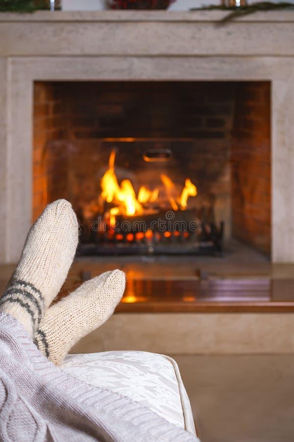 无法认出的妇女的脚或人温暖的白色被编织的袜子的和格子花呢披肩在壁炉前面 舒适轻松不可思议 库存照片
