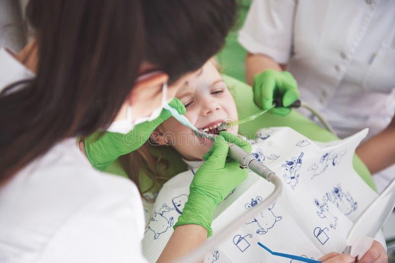无法认出的小儿科牙医和辅助制造的考试方法的手微笑的逗人喜爱的女孩的 免版税库存照片