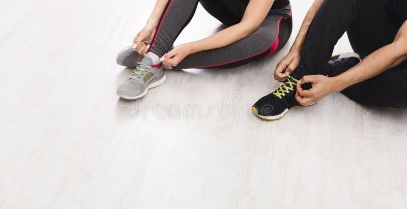 无法认出的栓在运动鞋的男人和妇女鞋带在训练前 免版税图库摄影