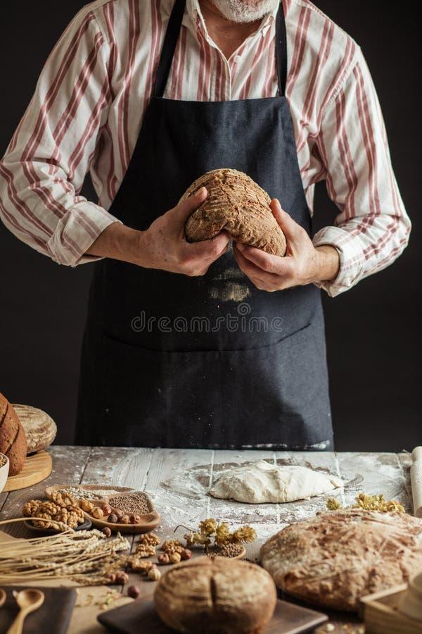 无法认出的面包师拿着在手中新近地被烘烤的土气有机面包 免版税库存图片