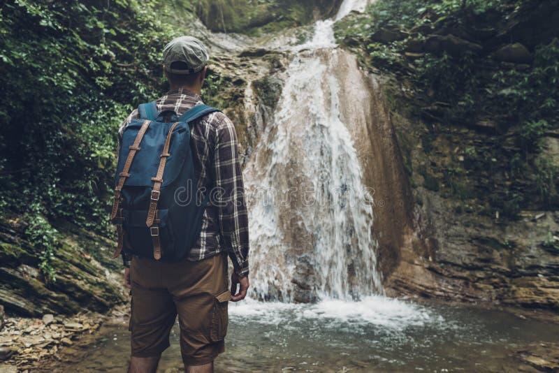 无法认出的年轻人到达了目的地和瀑布享用视图  远足冒险概念的旅途 图库摄影