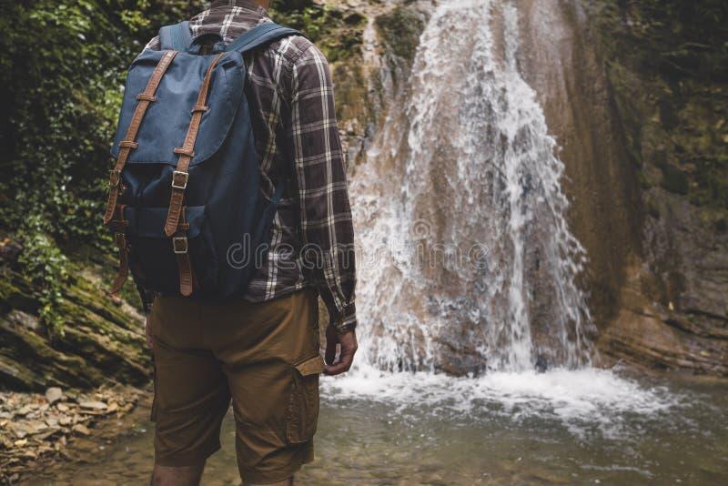 无法认出的年轻人到达了目的地和瀑布享用视图  远足冒险概念的旅途 免版税库存图片