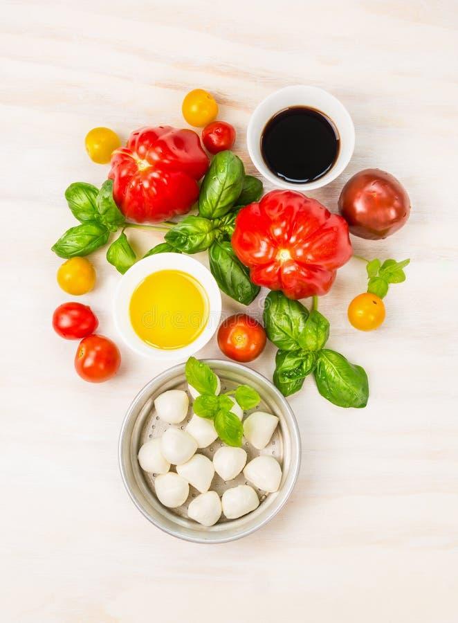 无盐干酪蕃茄与蓬蒿叶子、油和香醋,在白色木背景的准备的沙拉成份 免版税库存照片