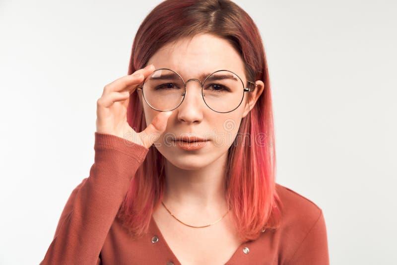 无精神年轻学生在接受检查的一个坏成绩以后皱眉 拿着妇女的美丽的玻璃新 库存照片