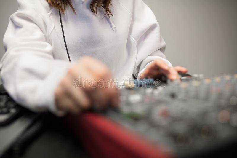 无线电主人的中央部位使用音乐搅拌器的在演播室 免版税库存图片