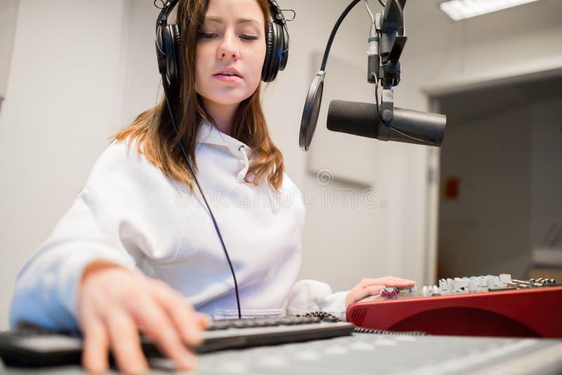 无线电骑师佩带的耳机在演播室 库存照片
