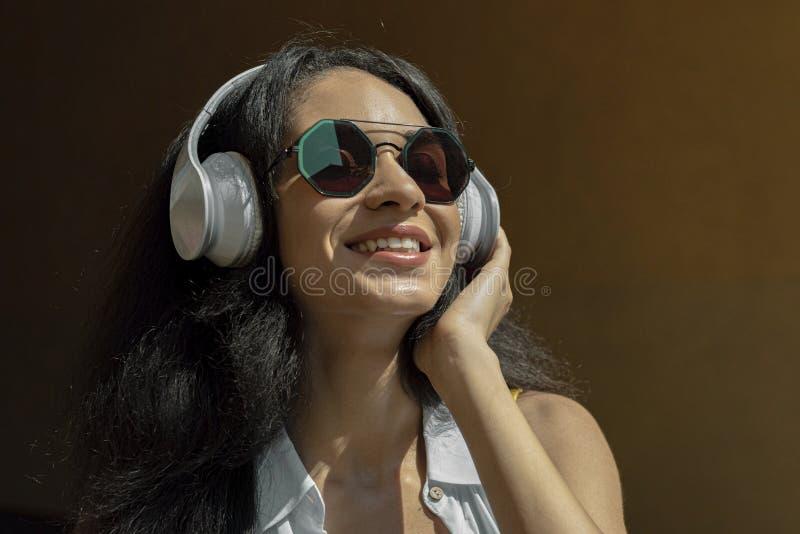 无线耳机的美丽的愉快的女孩享受音乐的 免版税库存照片