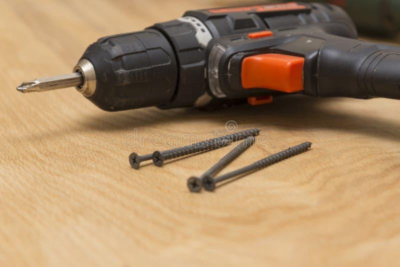 无线螺丝刀和自动攻丝螺杆在木背景,修理工作,特写镜头题材  库存图片