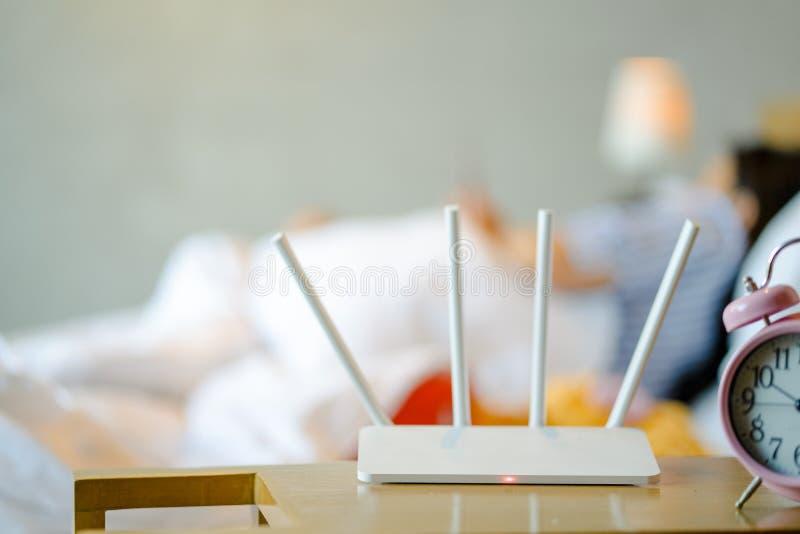 无线路由器和使用在卧室的年轻人一个智能手机在 库存图片