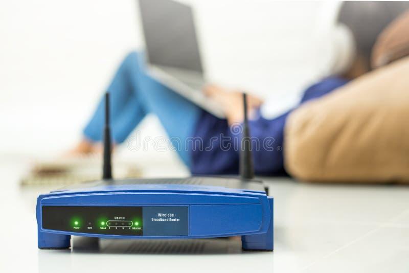 无线路由器和孩子使用一台膝上型计算机在家 路由器无线 免版税库存照片
