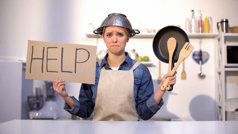 无经验的主妇请求在烹调的帮忙,在头,笑话的佩带的罐 库存照片