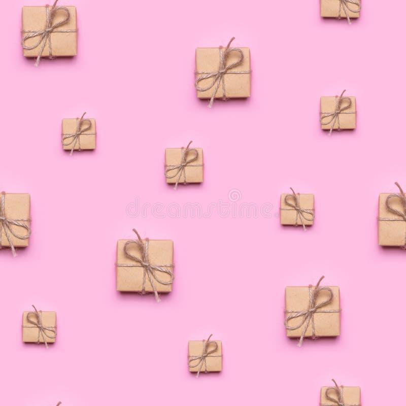 无缝的样式在牛皮纸包裹的由礼物制成在桃红色背景 免版税库存图片