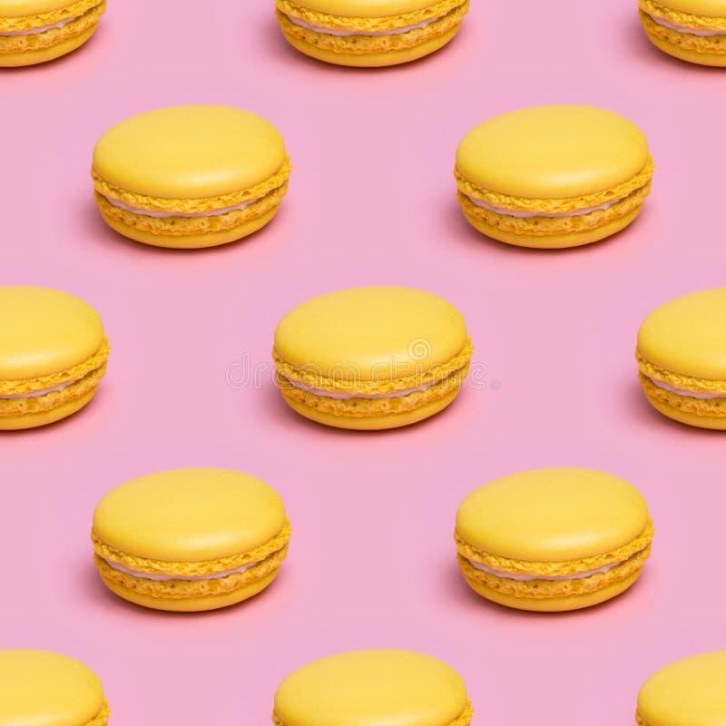无缝的样式用在桃红色背景的黄色macaron曲奇饼 库存图片