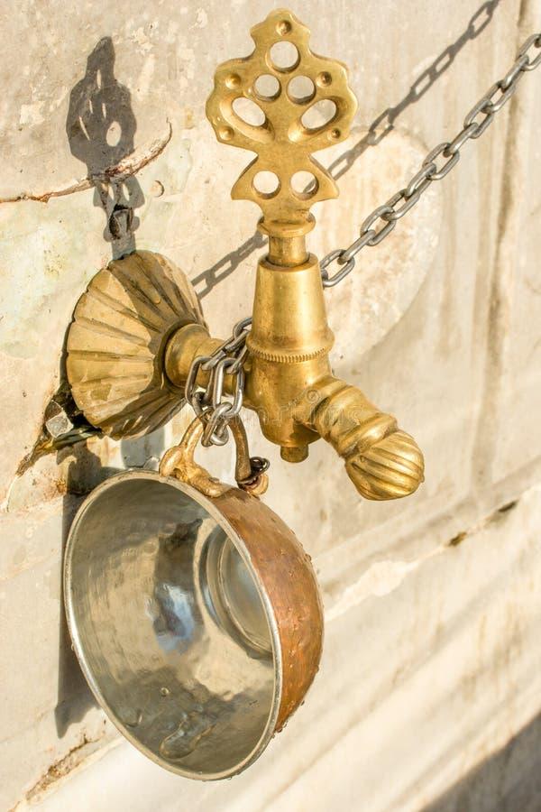 无背长椅古色古香的喷泉水龙头 库存图片