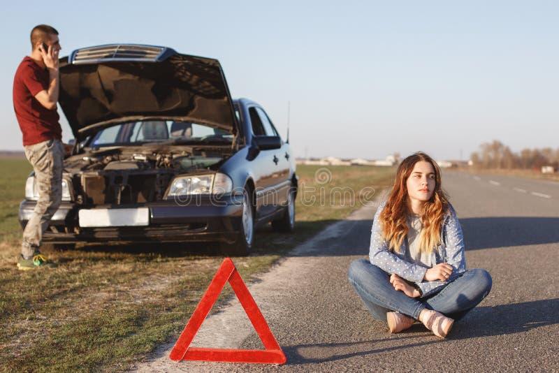 无能为力的夫妇在路停止有故障的汽车 绝望男性通过手机叫某人,请求帮忙,当立场ne时 库存图片
