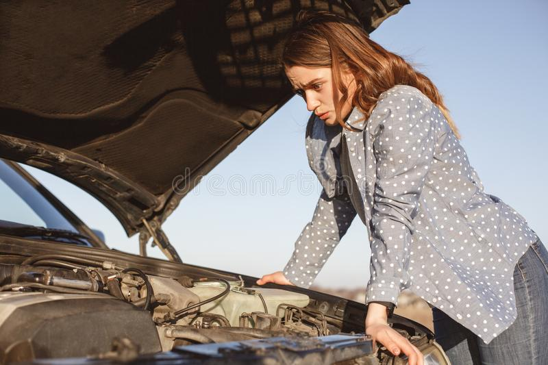 无能为力的女性绝望地看被打开的汽车敞篷,有在路的故障,能` t解决问题,冲击了表示,需要他 免版税图库摄影