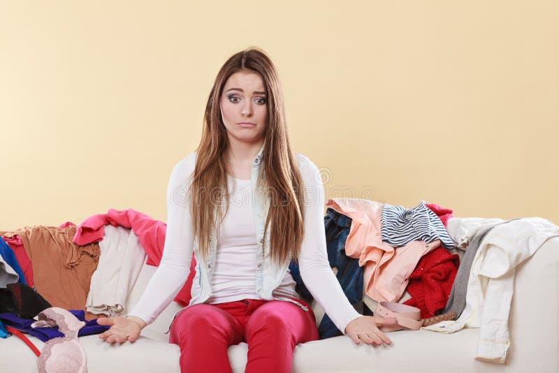 无能为力的妇女坐沙发在杂乱屋子家里 免版税库存图片