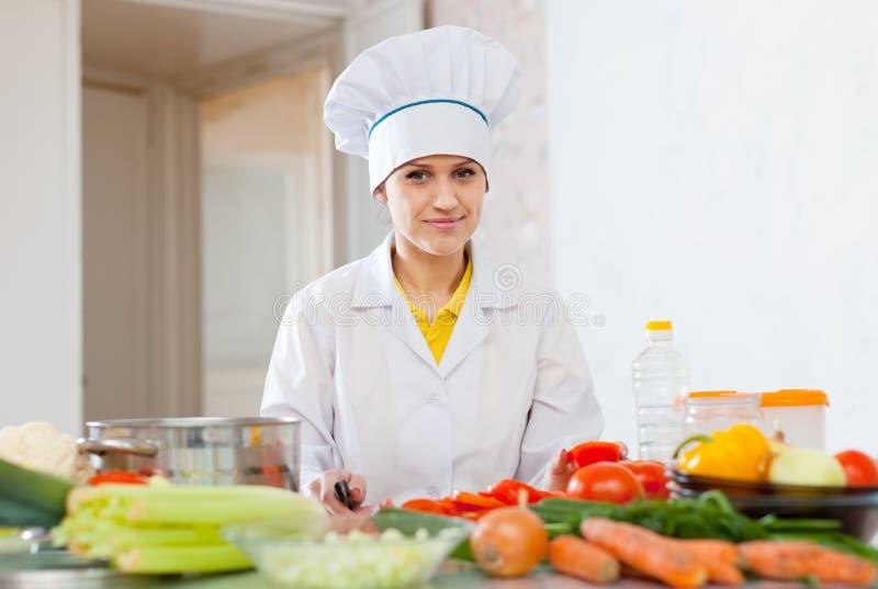 无边女帽的厨师与蕃茄和其他菜一起使用 库存图片