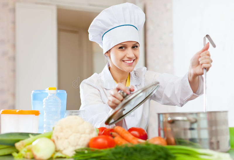 无边女帽的女性厨师在厨房 免版税库存图片