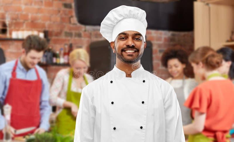 无边女帽的愉快的男性印度厨师在烹饪课 图库摄影