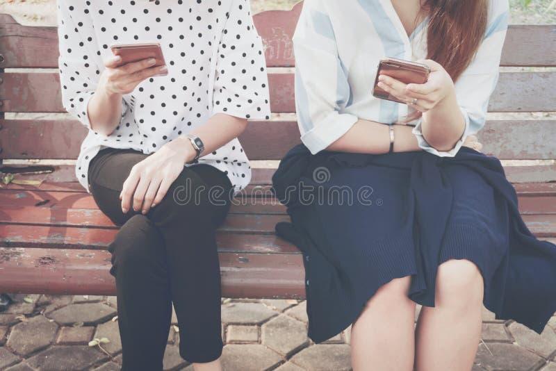 无兴趣片刻的两名妇女与在关系无积极性和使用新技术的室外,概念的巧妙的电话 免版税库存图片