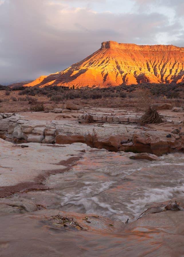 日出光在与漫过砂岩壁架的维尔京河的飓风Mesa发光在前景 库存图片