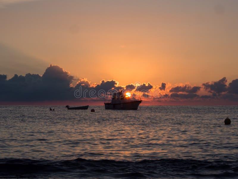 日出和小船在地中海 潘泰莱里亚海岛,意大利 库存照片