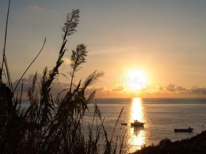 日出和小船在地中海 潘泰莱里亚海岛,意大利 免版税库存照片