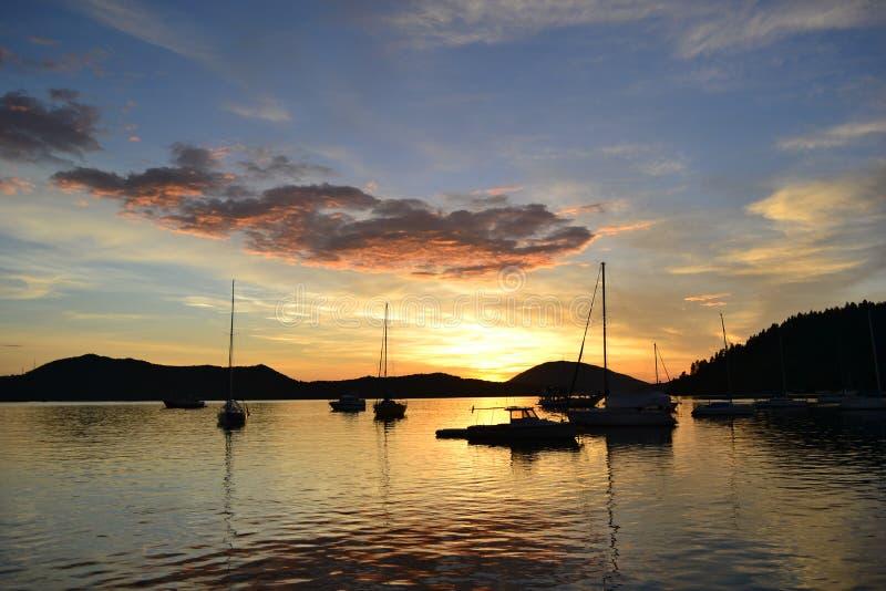 日出和小船在海 免版税库存图片