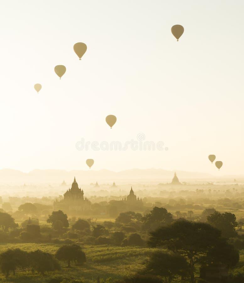 日出和热空气气球飞行在有薄雾的Bagan,缅甸 免版税库存图片