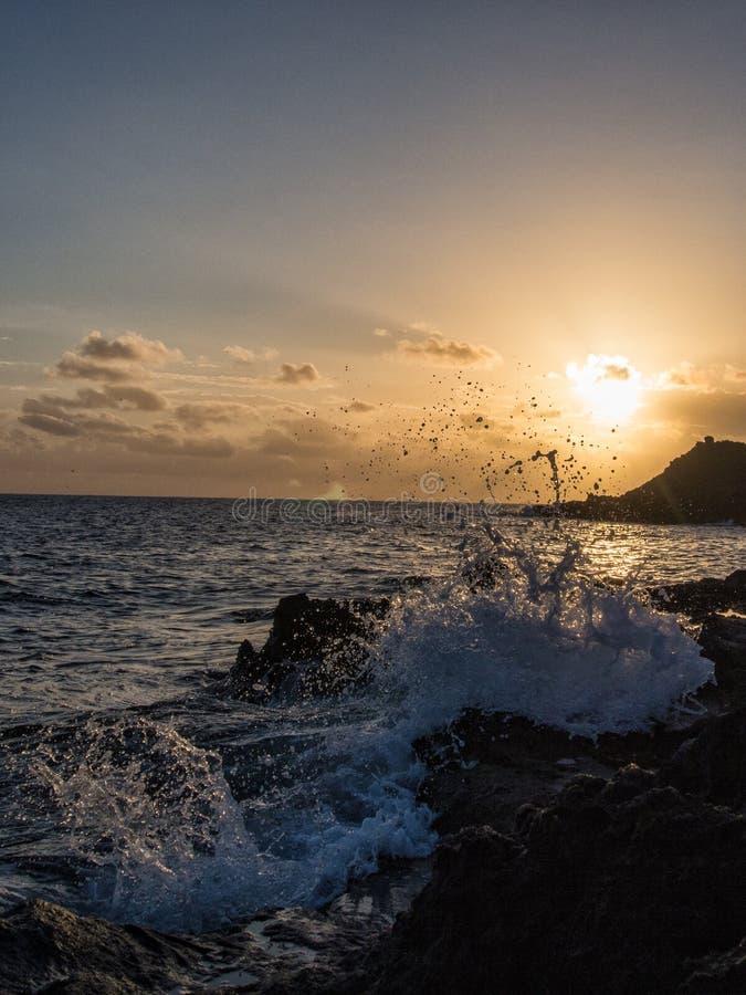 日出在岩石,潘泰莱里亚,意大利的波浪断裂 免版税库存图片