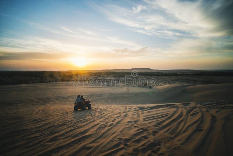 日出在沙漠 与两个ATV骑自行车的人的场面 游人在越野ATV乘坐通过越南沙漠的沙丘 免版税库存照片