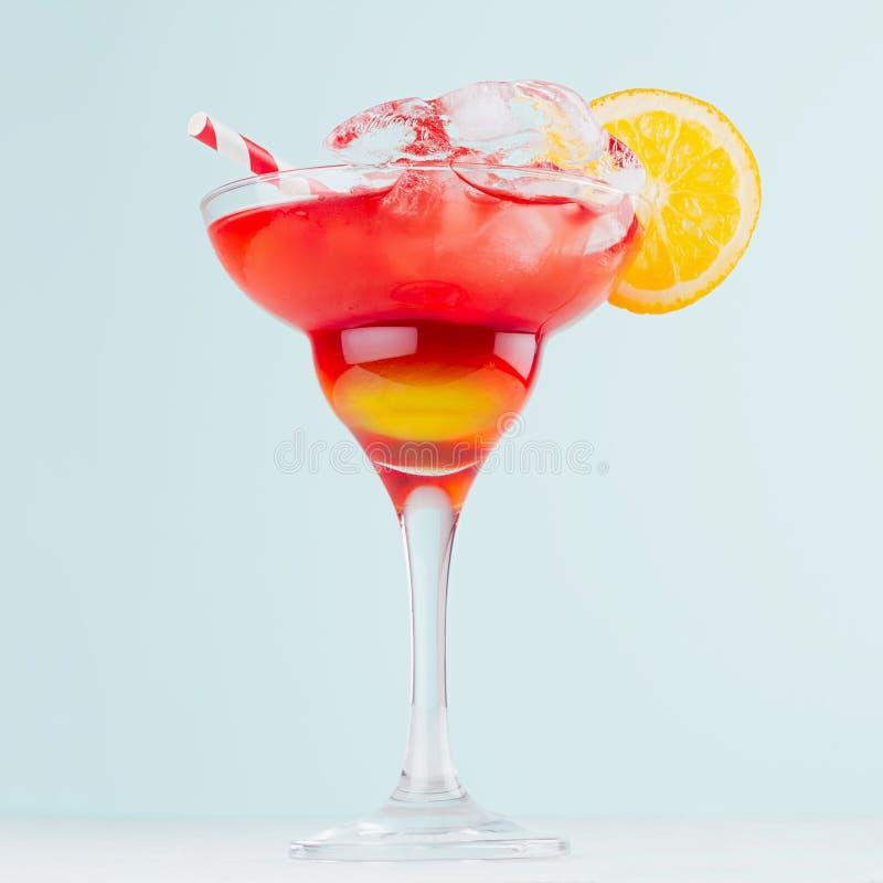 日出层状红色,黄色饮料用桔子,秸杆,在典雅的玻璃的冰块在淡色蓝色背景,白色木桌 免版税库存照片