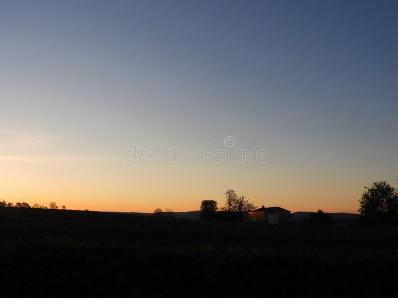 日出峰顶从与杆谷仓剪影的小山的后面 免版税库存照片
