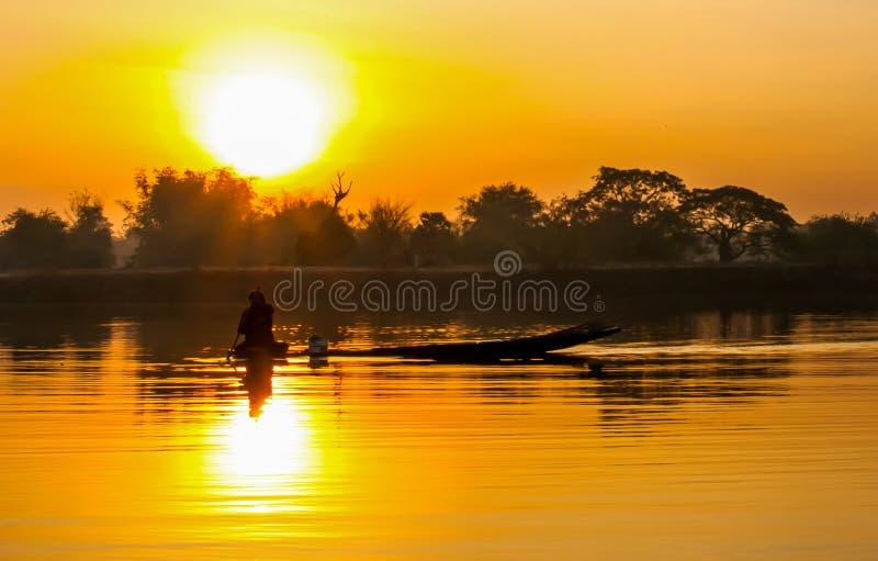 日出渔夫和充气救生艇 库存图片