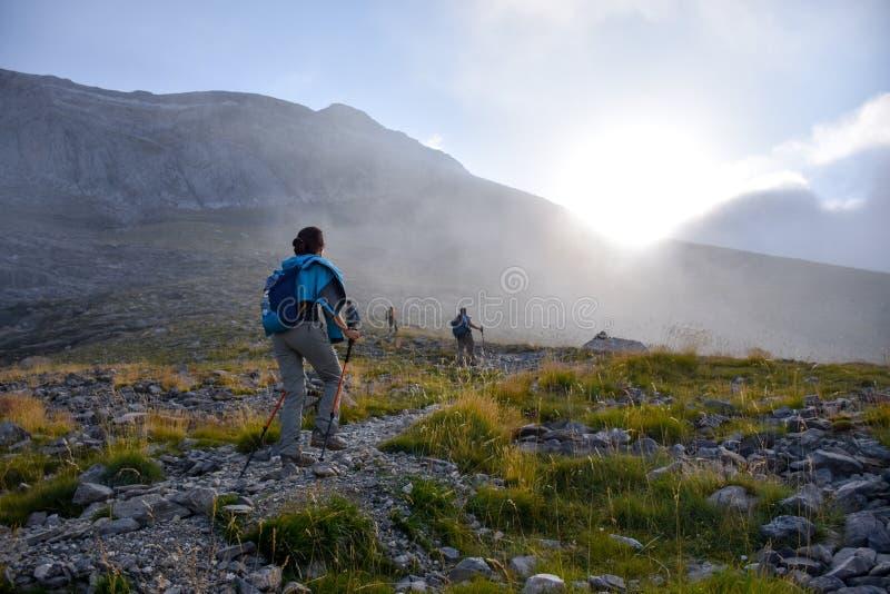 日出的山远足者在一条岩石道路 免版税库存照片