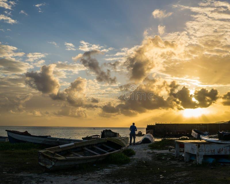 日出的牙买加渔夫与渔船 免版税库存照片