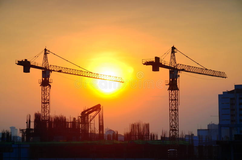 日出的起重机建筑 图库摄影