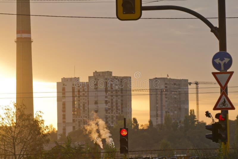 日出的TPP热电厂 有烟窗的精炼厂 从工厂的烟污染环境 高红色和白色t 图库摄影