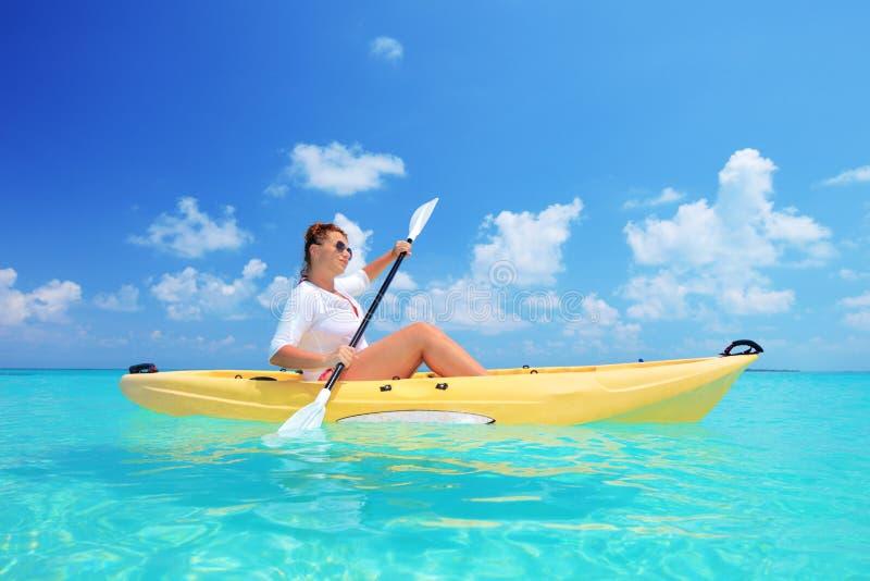 日划皮船的晴朗的妇女 库存图片