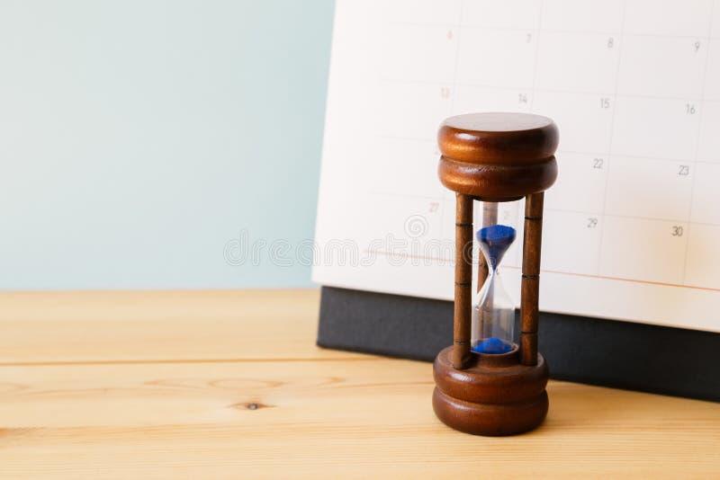 日历和滴漏在桌,企业日程表概念上 免版税库存照片