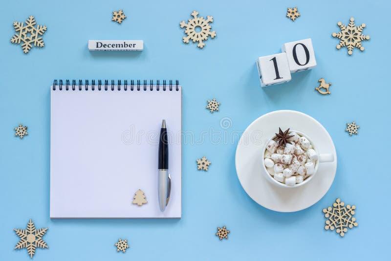 日历12月10日杯子可可粉和蛋白软糖,空的开放笔记薄 库存图片
